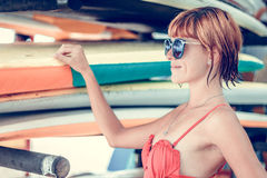 Молодая сексуальная девушка в красном купальнике - серфер при доска прибоя представляя на пляже Dua Nusa, тропический остров Бали Стоковое Фото