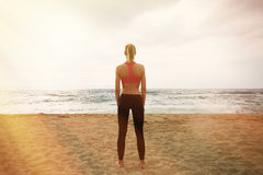 Молодая сексуальная девушка делая разминкой спорта пустой пляж песка Женщина фитнеса тратя море активного времени встречи внешнее Стоковые Изображения