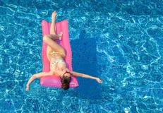 Молодая сексуальная женщина брюнет загорая на раздувном тюфяке в бассейне стоковые изображения