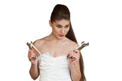 Молодая сексуальная женщина в белом платье держащ wrenchs в ее оружиях Стоковое Изображение