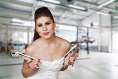 Молодая сексуальная женщина в белом платье держащ wrenchs в ее оружиях Стоковые Фото