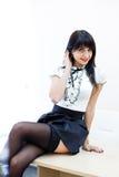 Молодая сексуальная женщина в черных чулках сидя на таблице в офисе Стоковые Фотографии RF