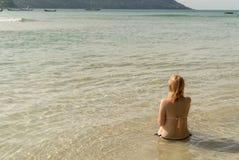 Молодая сексуальная женщина загорая в море Стоковые Фото