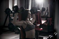 Молодая сексуальная разминка женщины фитнеса с гантелями в спортзале Стоковое Фото