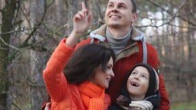 Молодая семья в древесинах Мама показывает knar к его сыну видеоматериал