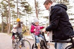 Молодая семья в теплых одеждах задействуя в парке осени Стоковые Изображения RF