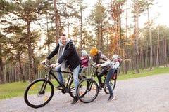 Молодая семья в теплых одеждах задействуя в парке осени Стоковые Фото