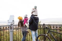 Молодая семья в теплых одеждах с велосипедом в парке осени Стоковое фото RF
