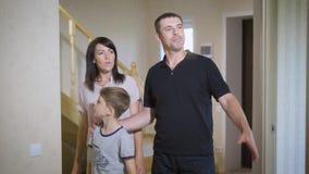 Молодая семья из трех человек входя в их новый дом Обсуждать человека и женщины акции видеоматериалы