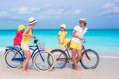 Молодая семья из четырех человек ехать велосипеды на тропическом пляже песка Стоковое Изображение