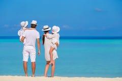 Молодая семья из четырех человек на белом пляже Стоковые Изображения