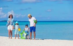 Молодая семья из четырех человек на каникулах пляжа Стоковое фото RF