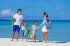 Молодая семья из четырех человек на каникулах пляжа стоковые фотографии rf