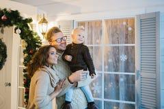 Молодая семья - мама, папа и сын стоят рядом с окном Стоковые Изображения