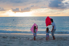Молодая семья наслаждаясь заходом солнца на пляже Стоковое фото RF