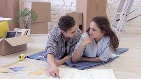 Молодая семья обсуждает интерьер их новой квартиры сток-видео