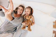 Молодая семья принимая selfie с smartphone в кровати Стоковая Фотография RF