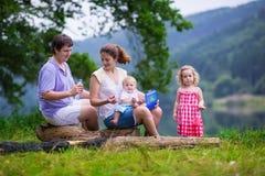 Молодая семья при дети на озере Стоковая Фотография