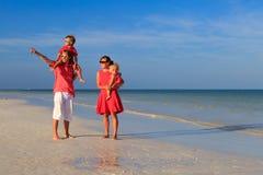 Молодая семья при 2 дет идя на пляж Стоковые Фотографии RF