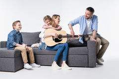 Молодая семья при 2 дет сидя совместно на кресле и играя гитару Стоковые Изображения RF