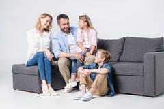Молодая семья при 2 дет сидя совместно на софе и усмехаться Стоковое Изображение