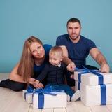 Молодая семья распаковывая настоящие моменты Стоковые Фотографии RF