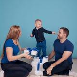Молодая семья распаковывая настоящие моменты Стоковое Изображение RF