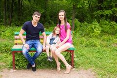 Молодая семья сидя на стенде в парке лета Стоковые Фото