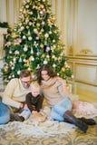 Молодая семья сидя под рождественской елкой Стоковое Изображение RF