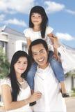 Молодая семья стоя около их нового дома стоковая фотография rf