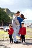Молодая семья с малыми детьми на гавани в после полудня Стоковые Изображения
