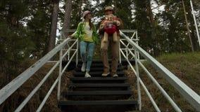Молодая семья с ребенком вниз с лестниц к морю сток-видео