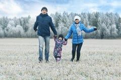 Молодая семья с ребенком идет в поле зимы Стоковое Фото