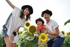 молодая семья усмехается с полем солнцецвета Стоковые Изображения RF