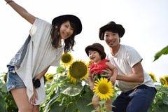 молодая семья усмехается с полем солнцецвета Стоковое фото RF