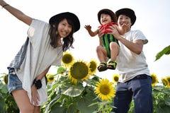 молодая семья усмехается с полем солнцецвета Стоковое Изображение RF