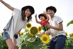 молодая семья усмехается с полем солнцецвета Стоковое Изображение