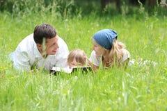 Молодая семья читая библию стоковое изображение