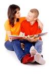 Молодая семья читая книгу совместно Стоковые Изображения