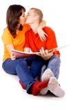 Молодая семья читая книгу совместно Стоковые Фото