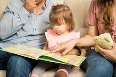 Молодая семья читая книгу совместно Стоковое Изображение RF