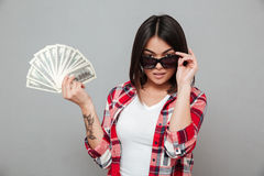 Молодая серьезная женщина держа деньги над серой стеной Стоковое Фото
