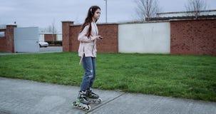 Молодая симпатичная девушка при красивые волосы и наушники сидя на улице страны с зеленой травой Девушка отправляя СМС на умном видеоматериал