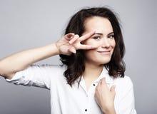 Молодая симпатичная женщина показывая победу или знак мира Стоковая Фотография RF