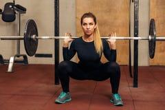 Молодая сильная девушка в спортзале делая сидение на корточках Стоковые Изображения RF