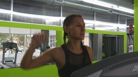 Молодая сильная женщина с совершенным телом фитнеса в sportswear бежать на третбане в спортзале Девушка работая во время cardio акции видеоматериалы