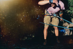 Молодая смертная казнь через повешение альпиниста на утесе на веревочке и взгляды где-то на стене Весьма концепция мероприятий на Стоковое фото RF