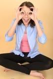 Молодая смешная шальная женщина сидя на поле вытягивая придурковатое выражение лица Стоковые Изображения RF