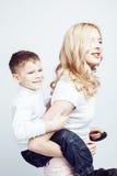 Молодая современная белокурая курчавая мать с милый сына представлять семьи совместно счастливый усмехаясь жизнерадостный на бело Стоковое Изображение RF