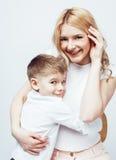 Молодая современная белокурая курчавая мать с милый сына представлять семьи совместно счастливый усмехаясь жизнерадостный на бело Стоковые Изображения RF